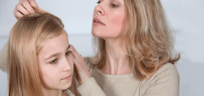 Luizen controle, vrouw controleerd haar dochter op luizen.